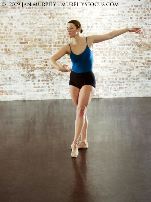 classical dance pose in studio, colour, ballet shoes, brick wall