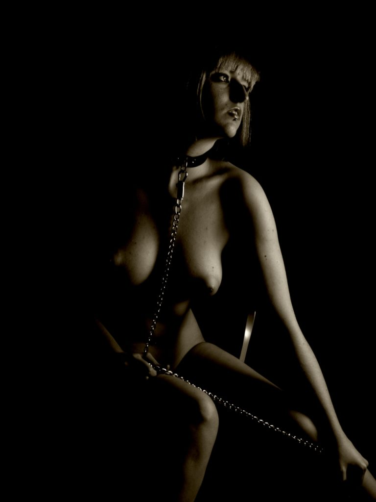 Seated female artistic nude model, playing with chain and collar