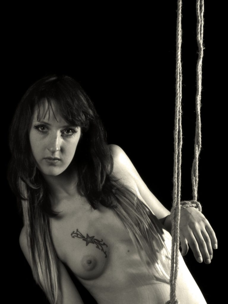 female figure model, ropes on wrists, staring at camera