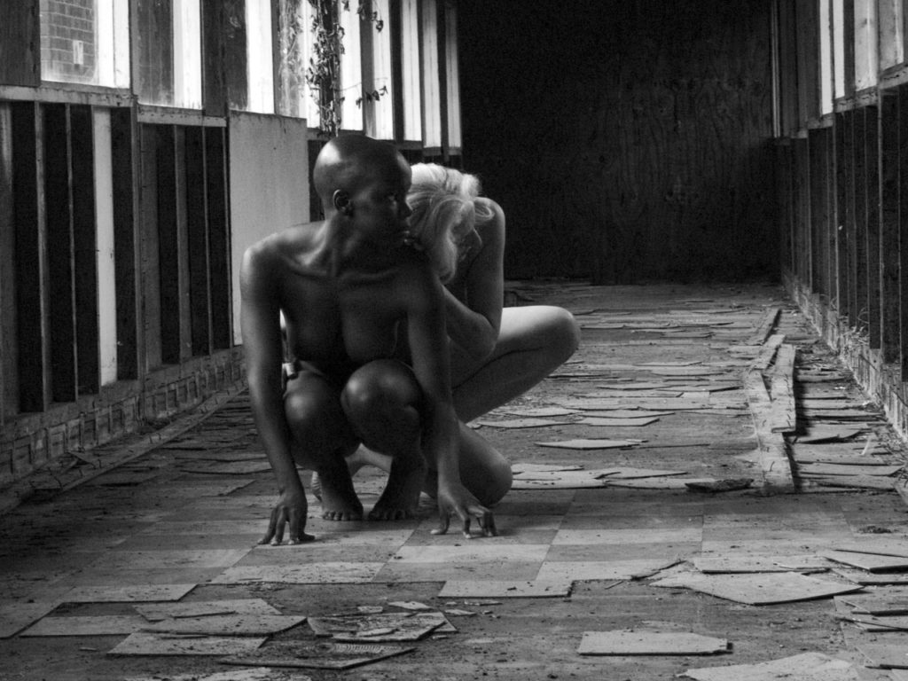 Two female naked forms, in derelict asylum crouching, one white figure, grey hair, one  black figure, bald
