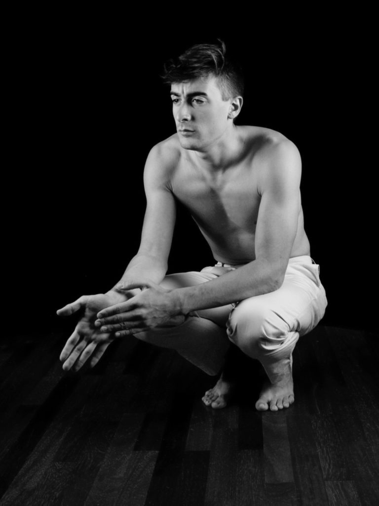 male model, topless, crouching, hands gently placed